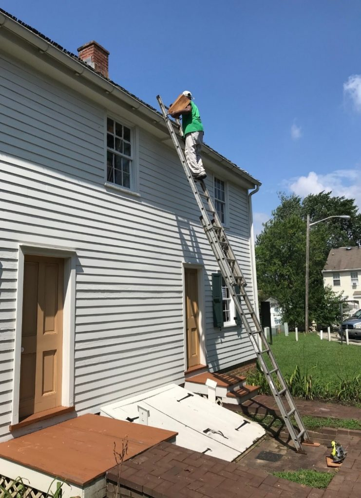 Roofer patching and performing repair work on the Peter Mott House